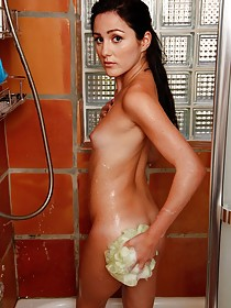 Flat-chested brunette soaping her tender pussy in the shower