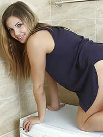 Thick brunette takes off her cute sleeveless get-up in the bathroom