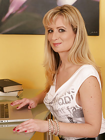 Mature blonde with bangs exposing her alluring holes while working