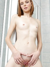 Skinny and flat-chested redhead teasing her awesome pussy on cam
